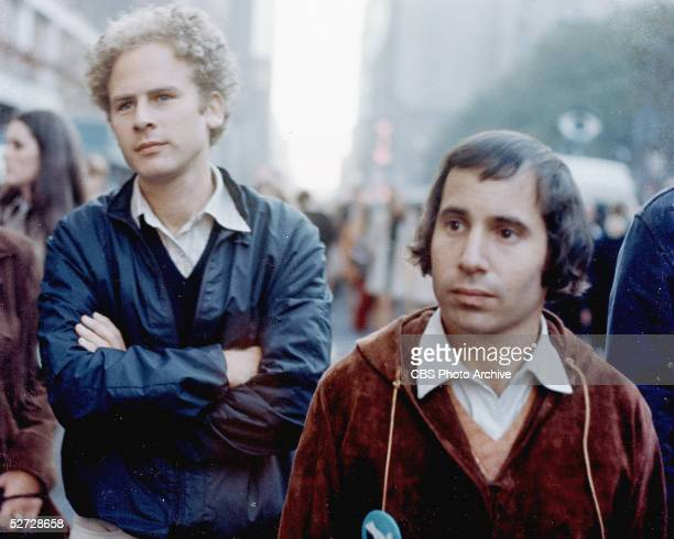 American folk and pop performers Art Garfunkel and Paul Simon stand on a street during the filming of a televison special called 'Songs of America'...