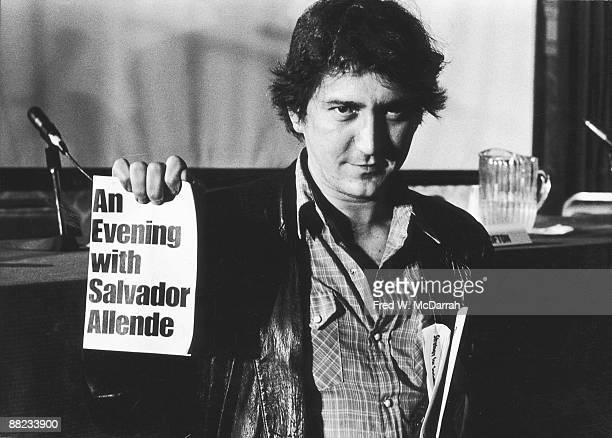 American folk musician and political activist Phil Ochs holds up a flyer that reads 'An Evening With Salvador Allende' the name of a benefit concert...