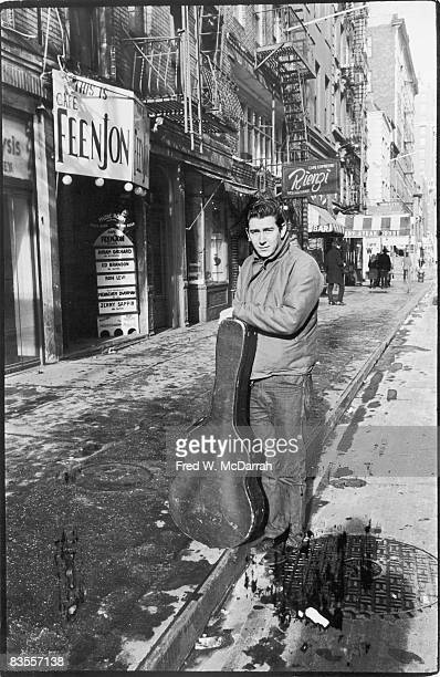 American folk musician and political activist Phil Ochs poses with his guitar outside the Cafe Feenjon on MacDougal Street New York New York January...