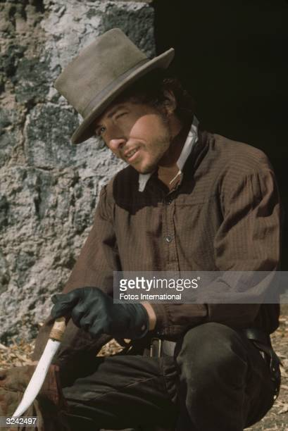 American folk rock singer and songwriter Bob Dylan wipes the blade of his dagger as he crouches in front of a doorway in a still from director Sam...