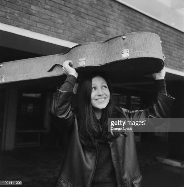 American folk singer and musician Julie Felix takes shelter beneath her guitar case on leaving London Airport in London England 12th July 1965