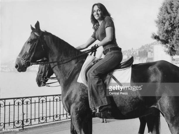 American folk singer Joan Baez riding a horse in Switzerland circa 1960