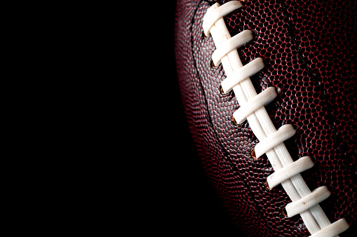 American football  and game day poster concept with close up on the texture of a ball with dramatic moody light with high contrast and copy space on a dark black background 1136080982