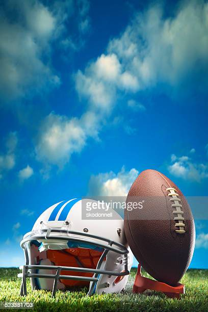 American Football and Helmet on Field Cloudscape Copy space