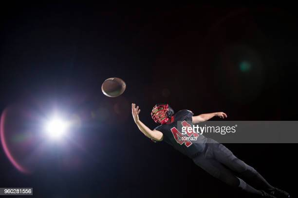 american football - catching the ball - safety american football player stock pictures, royalty-free photos & images