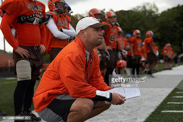 American football coach and players (focus on foreground)