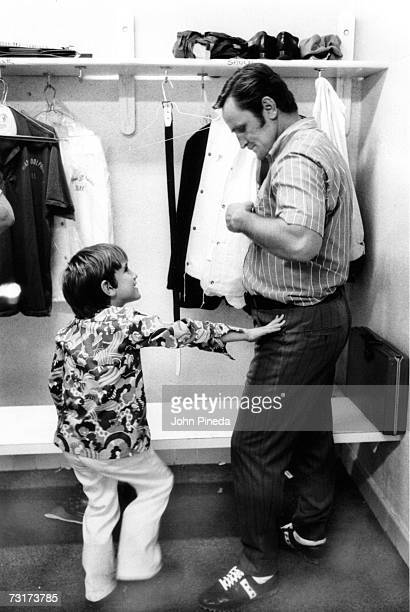 American football coach Don Shula dresses in the locker room as his son Mike stands with him Miami Florida 1971