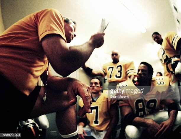 american football coach giving players pep talk in locker room - pep talk stock pictures, royalty-free photos & images