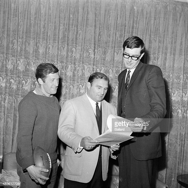 American football coach Hank Stram handing a contract to Bob Howfield and John Haslam to play for Kansas City Football Team 1968