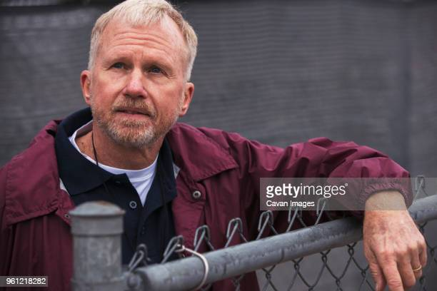 american football coach looking away while standing by fence in stadium - one senior man only stock pictures, royalty-free photos & images
