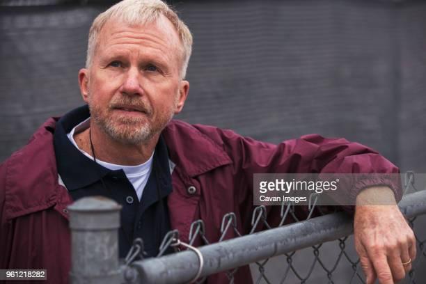 american football coach looking away while standing by fence in stadium - só um homem idoso - fotografias e filmes do acervo