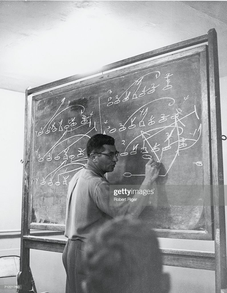 American football coach Vince Lombardi draws a play on the chalkboard during a team meeting, early 1960s.