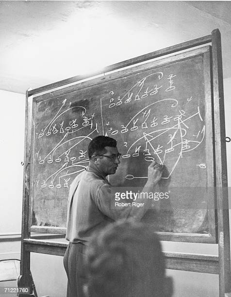 American football coach Vince Lombardi draws a play on the chalkboard during a team meeting early 1960s