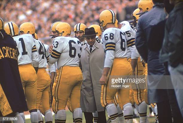 American football coach Vince Lombardi head coach and general manager for the Green Bay Packers stands with his players on the sidelines during a...