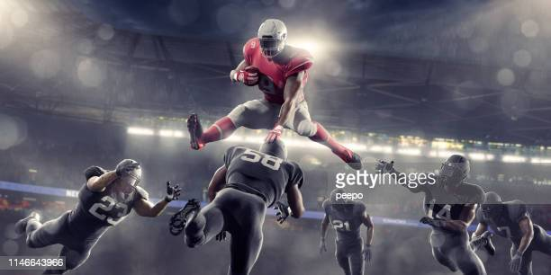 american football hero jumping over opponents during game in stadium - football player stock pictures, royalty-free photos & images