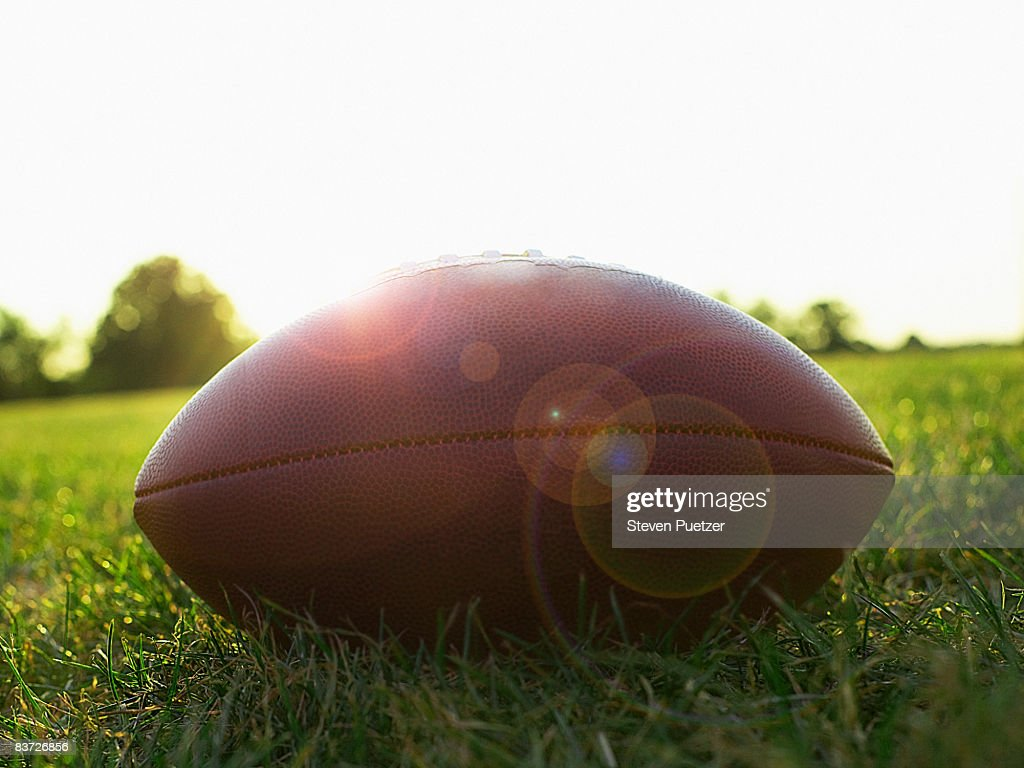 American football on grass, side view : Stock Photo