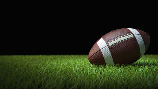 American football on green grass, on black background 1156305872