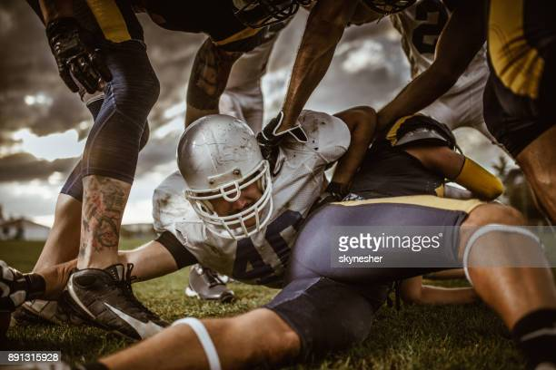 american football player among defensive players on a match. - football league stock pictures, royalty-free photos & images