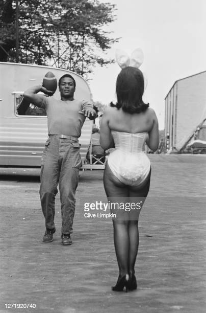 American football player and actor Jim Brown throws a ball for Bunny Girl Dolly Read on the set of the film 'The Dirty Dozen' at Elstree Studios, UK,...