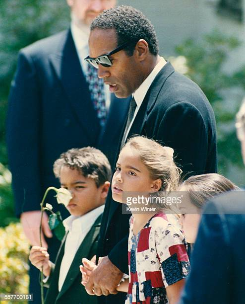 American football player and actor O J Simpson holding hands with his children Justin and Sydney at the funeral of their mother and his exwife Nicole...