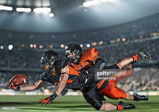 american football player being tackled by opponent - tackling stock pictures, royalty-free photos & images