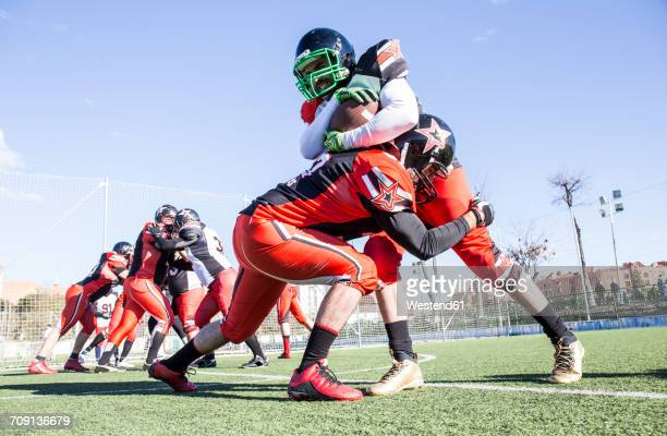 american football player being tackled by opponent player during a match - tackling stock pictures, royalty-free photos & images