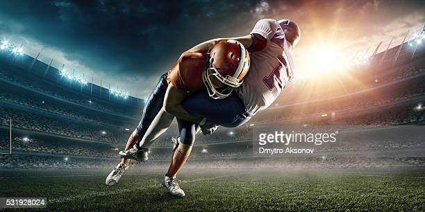 american football player being tackled - tackling stock pictures, royalty-free photos & images