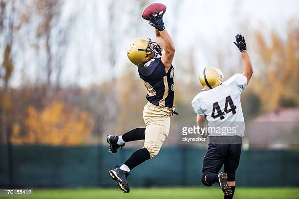 american football player catching a ball. - wide receiver athlete stock pictures, royalty-free photos & images