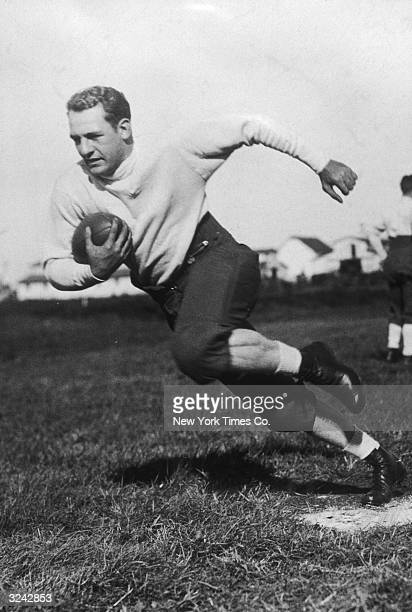 American football player Harold 'Red' Grange clutches a football to his chest while running during practice with the Chicago Bears at the Exposition...