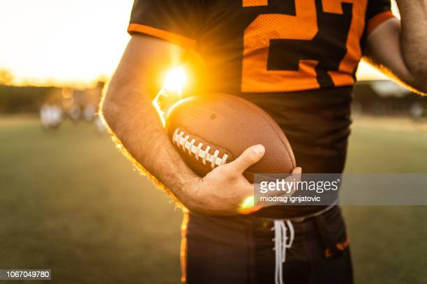 american football player holding ball - practicing stock pictures, royalty-free photos & images