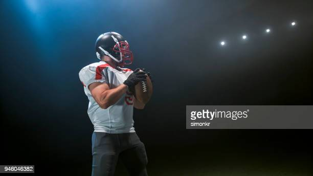 american football player holding ball - safety american football player stock pictures, royalty-free photos & images