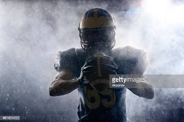 american football player in a haze and rain on black background. portrait - quarterback stock photos and pictures