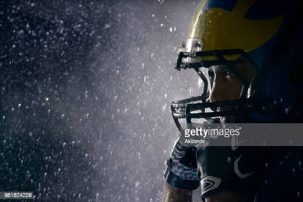 american football player in a haze and rain on black background. portrait close-up - quarterback stock photos and pictures