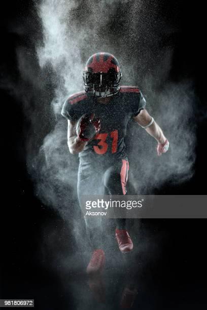 american football speler in een waas op zwarte achtergrond - football league stockfoto's en -beelden