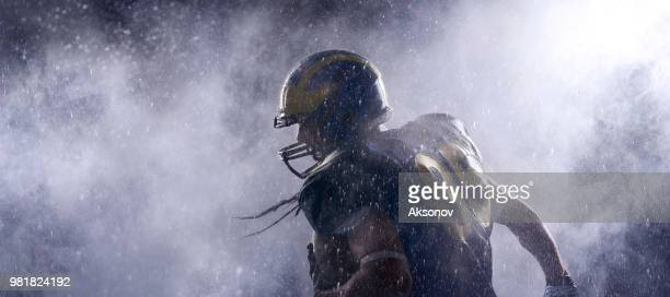 jugador del fútbol americano en una bruma sobre fondo negro. retrato - corredor jugador de fútbol americano fotografías e imágenes de stock