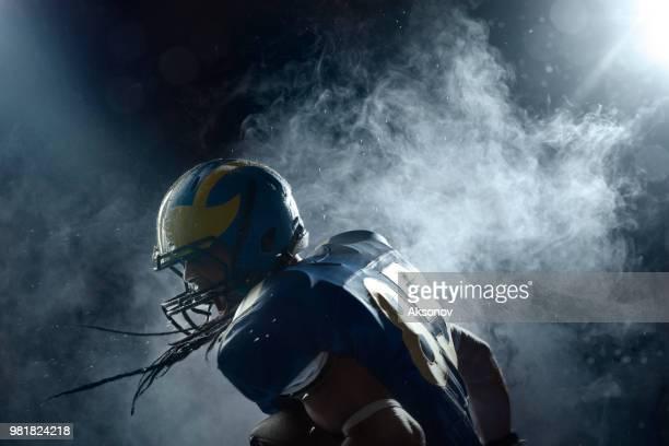 american football speler in een waas op zwarte achtergrond. portret - football league stockfoto's en -beelden