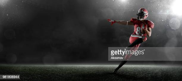 american football player in dark sport stadium - american football strip stock pictures, royalty-free photos & images