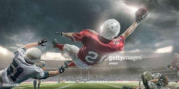 Jogador de futebol americano em façanhas para trás Mergulho de Apanhar a Bola