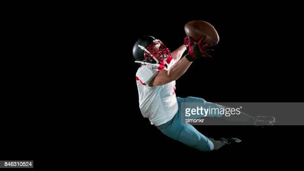 American football player in white jersey catching ball inthe air with one hand on black background