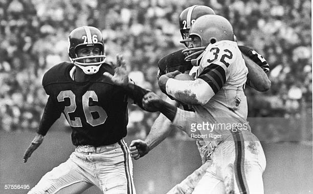 American football player Jim Brown of the Cleveland Browns tries to force his way past a pair of defensive players from the Pittsburgh Steelers...