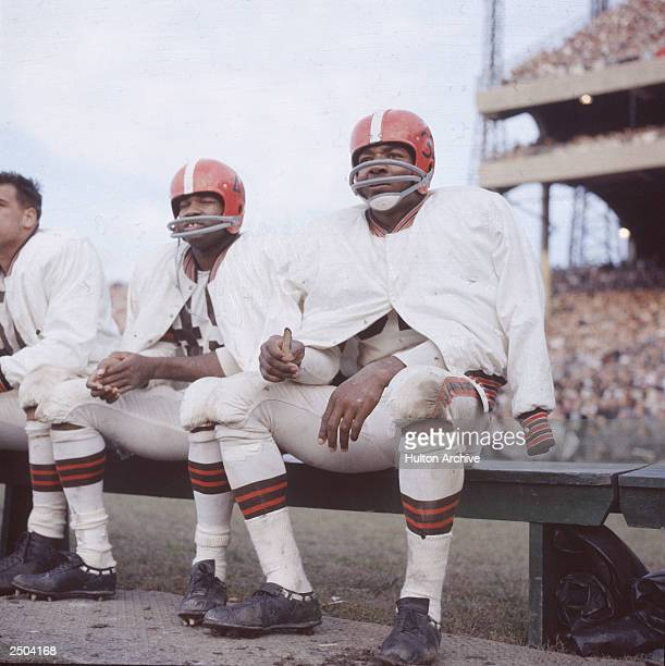 American football player Jim Brown sits on the bench during a game wearing his helmet and uniform for the Cleveland Browns circa 1960