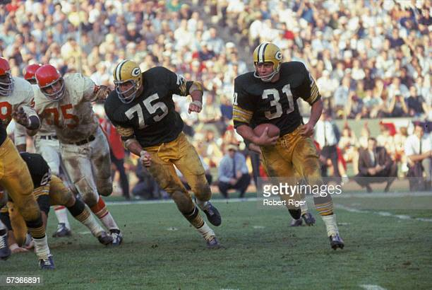 American football player Jim Taylor of the Green Bay Packers runs with the ball as teammate Forrest Gregg blocks for him during the first AFLNFL...