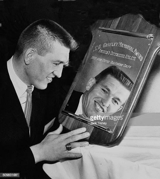American football player Johnny Unitas looks at his reflection in his SO Grauley Memorial Award for 'America's Outstanding Athlete' 1959