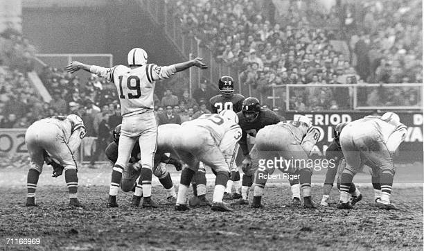 American football player Johnny Unitas quarterback for the Baltimore Colts holds his arms out to request quiet from the crowd for the final drive in...