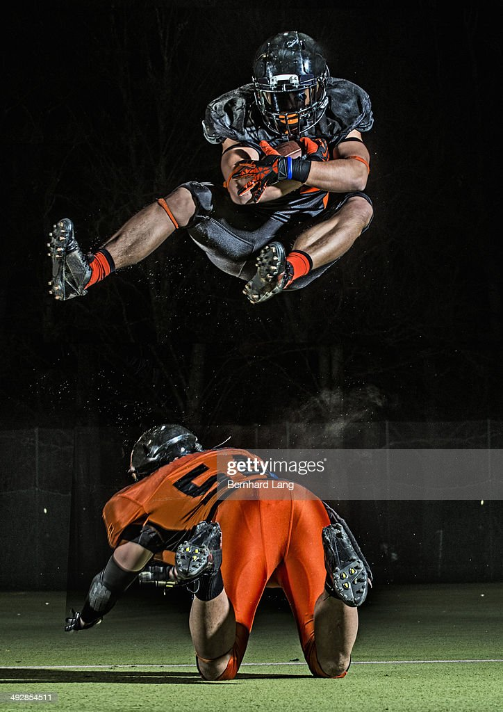 American football player jumping in mid-air : Stock Photo