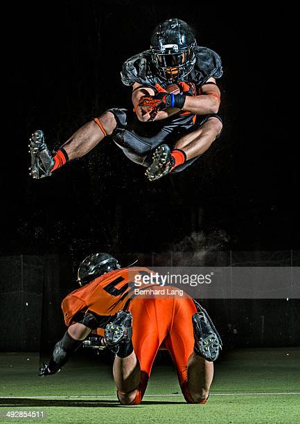 american football player jumping in mid-air - defensive tackle american football player stock pictures, royalty-free photos & images