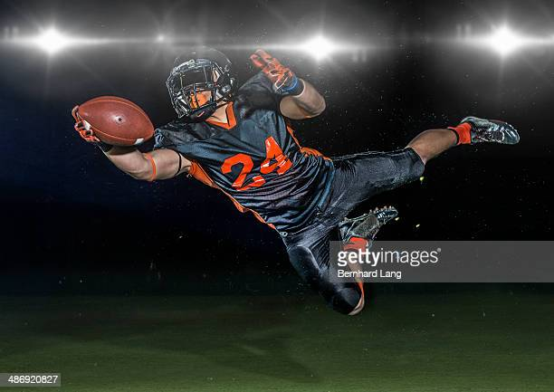 american football player jumping to catch football - playing football stock pictures, royalty-free photos & images