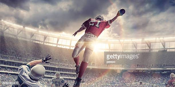 american football player jumps to catch ball during game - catching stock pictures, royalty-free photos & images