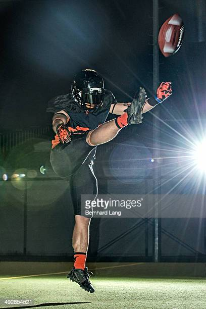 american football player kicking football - offensive tackle american football player stock photos and pictures
