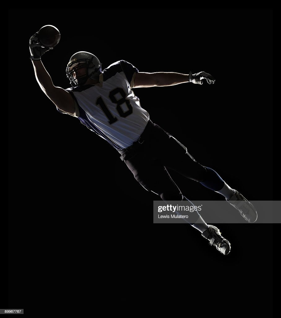 American Football player leaping to catch ball : Stock Photo